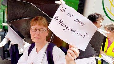 """Frau mit Regenschirm und Zettel """"wo bleibt unser Rettungsschirm?"""""""
